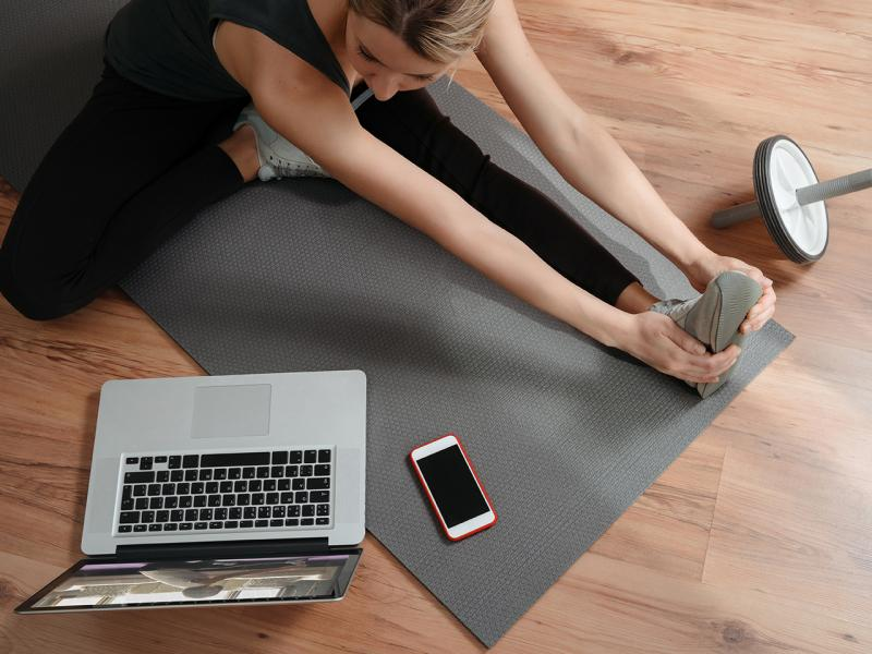 Young caucasian woman doing online workout and repeating exercises from online training on laptop. Flexibility and strength.Wellness and home fitness concept